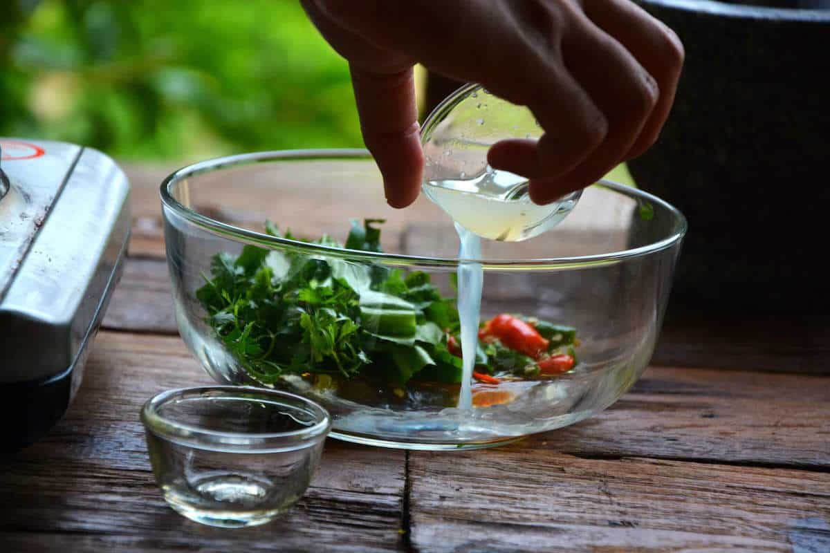 pouring fresh squeezed lime into bowl for tom yum recipe prep